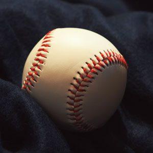 A baseball on top of a black sheet.